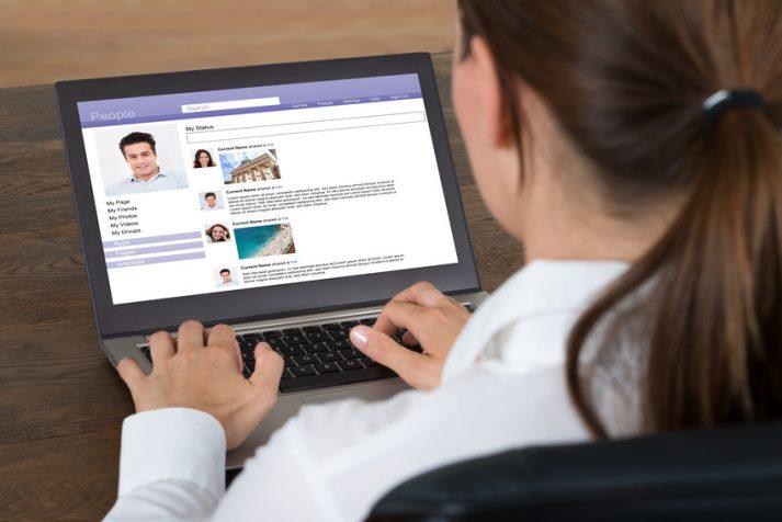 Frau chattet im social web am Laptop