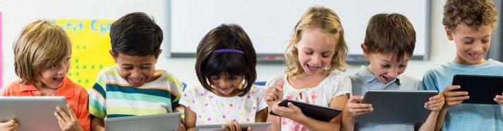 6 Schulkinder nebeneinander mit einem Tablet in der Hand