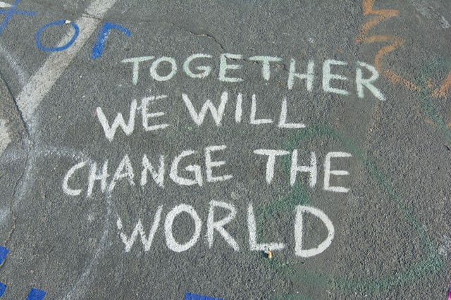 Together we will change the world written on the pavement with chalk