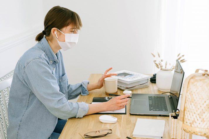 Frau mit Atemschutzmaske am Schreibtisch von ihrem Laptop