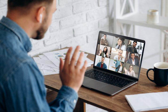 Bild eines Mannes, der am Laptop mit Teamkollegen per Videochat verbunden ist